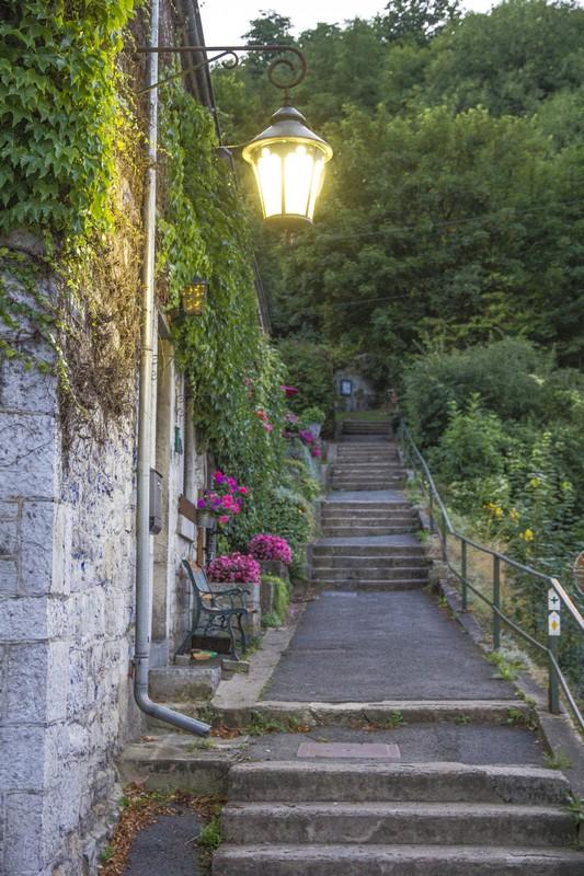 scalinata antica con lampione acceso e fiori fuxia
