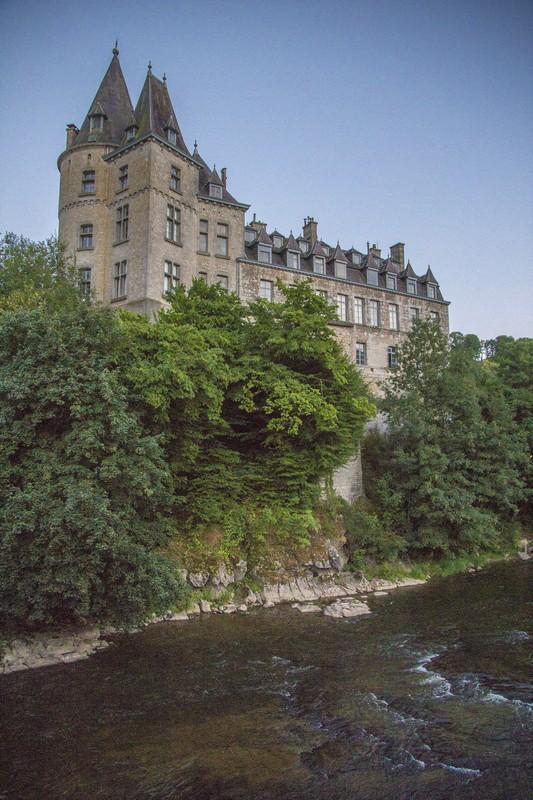 castello a picco sul fiume con alberi