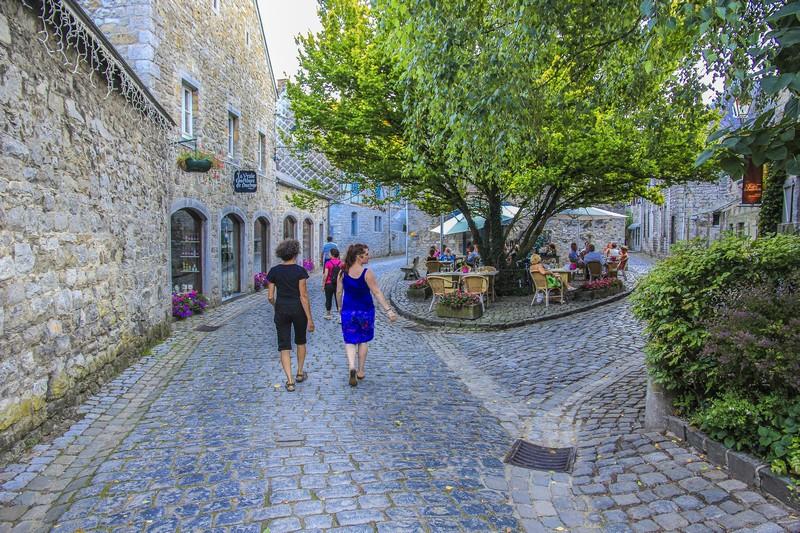 persone che passeggiano nelle strade acciottolate fra edifici di pietra della città vecchia