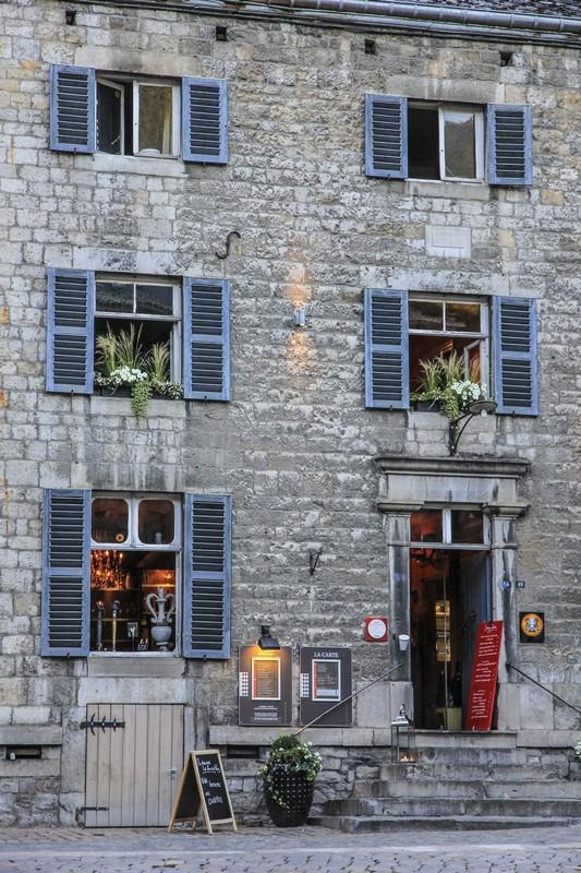 facciata antica di ristorante con finestre con vasi di fiori e insegna