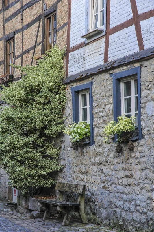 facciata in pietra di casa atica con panchina e vasi di fiori bianchi alle finestre