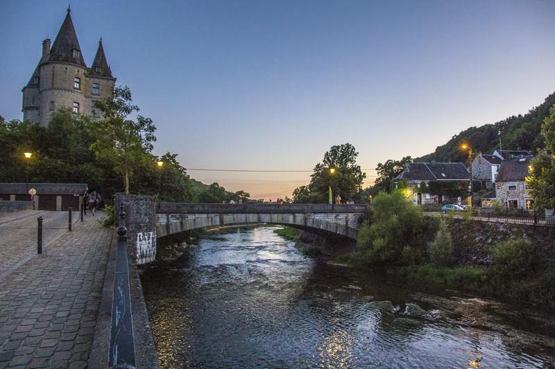 vista del fiume che passa sotto un ponte con vista sul castello e sula paese