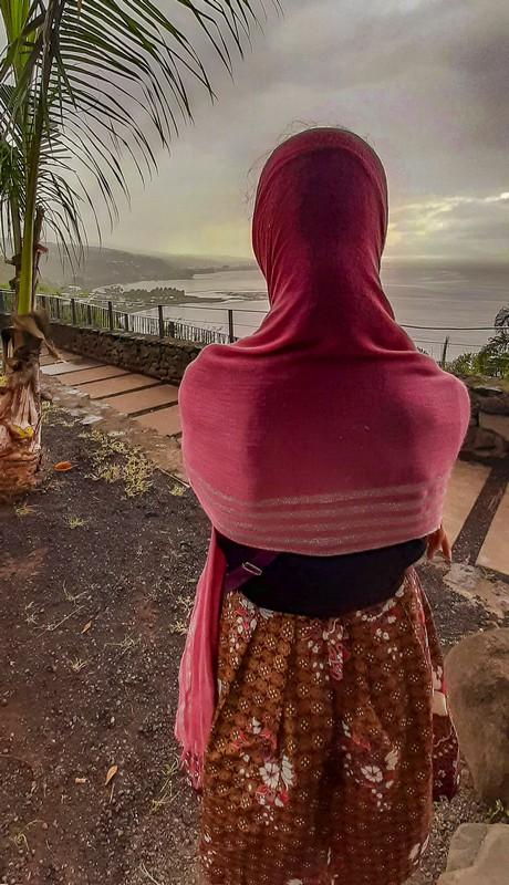 Ragazza si copre dalla pioggia guardando la terrazza panoramica e la costa sottostante
