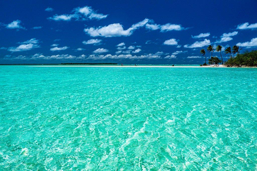 Mare turchese con spiaggia e palme in lontananza cielo azzurro e nuvolette bianche