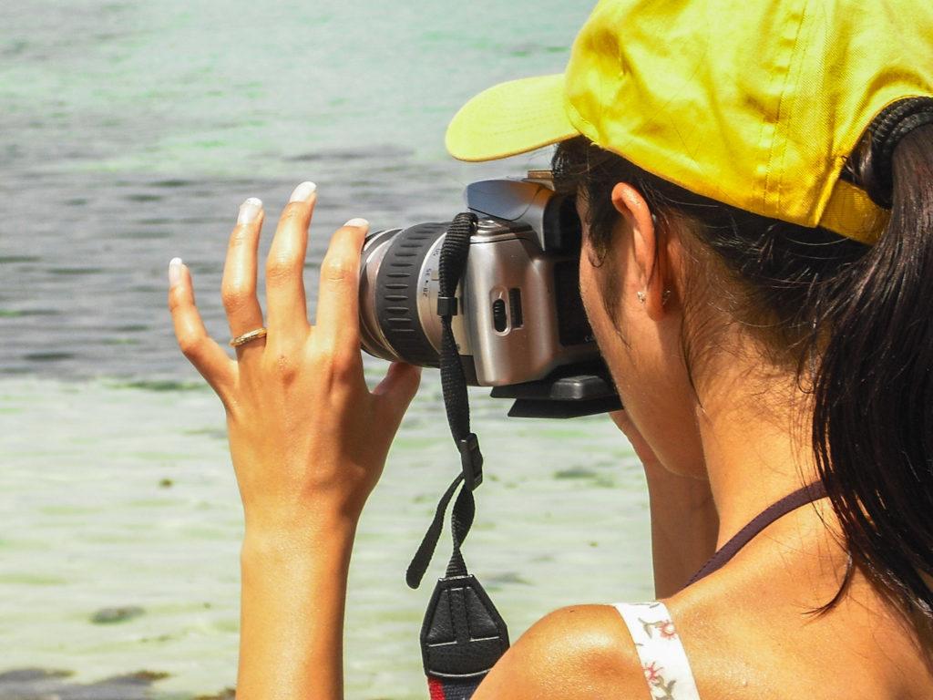 ragazza fotografa con vecchia reflex a pellicola