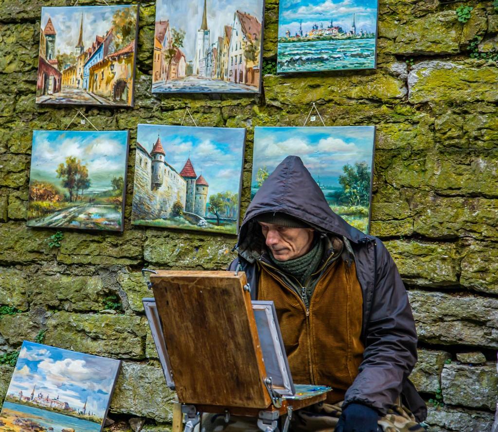 Artista di strada con quadri della città