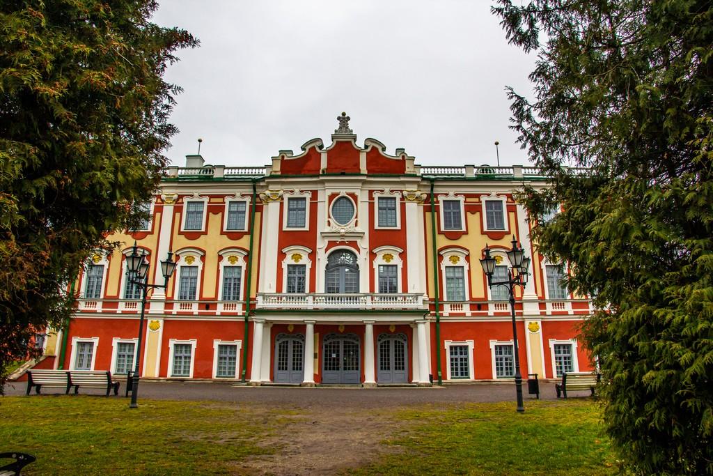 palazzo bianco e rosso dietro a due alberi
