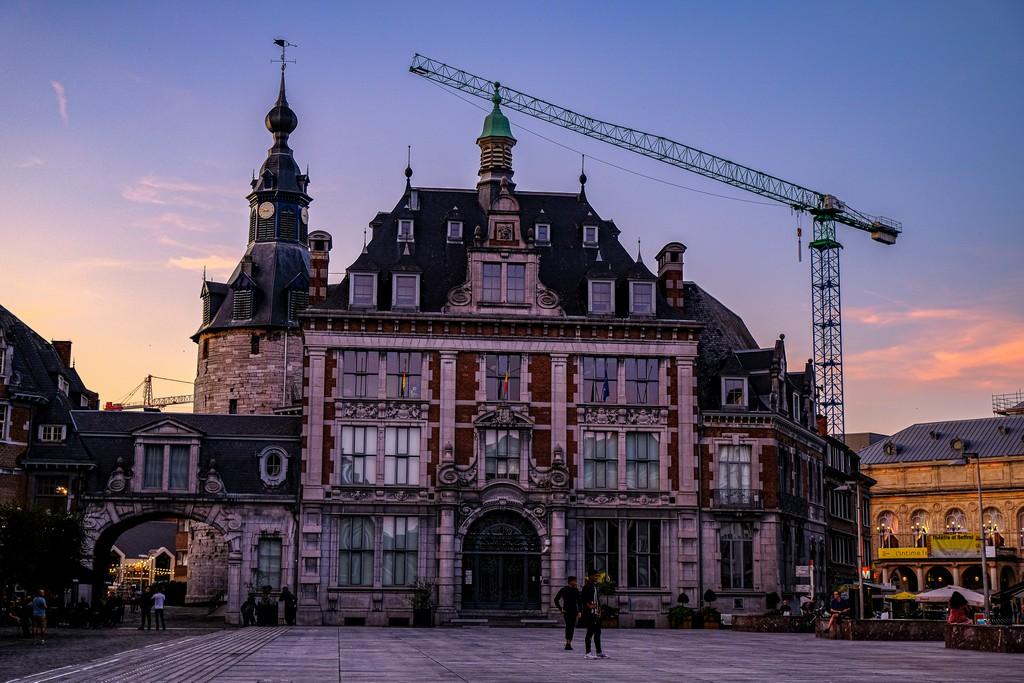 piazza principale con facciata di edificio e gru al tramonto