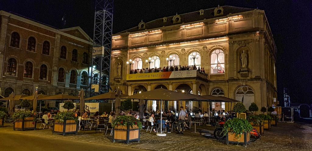 facciata di edificio di sera con tavolini in strada
