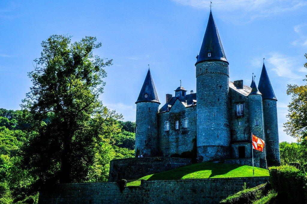 castello medievale in prato verde e cielo blu con bandiera
