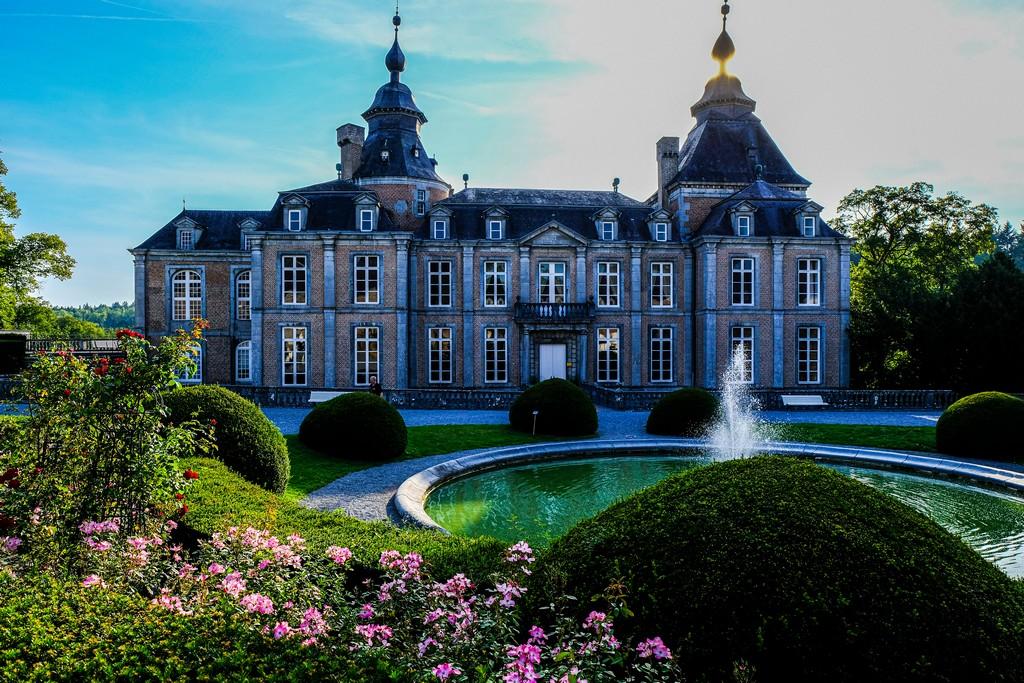 facciata del castello con fiori in primo piano e fontana