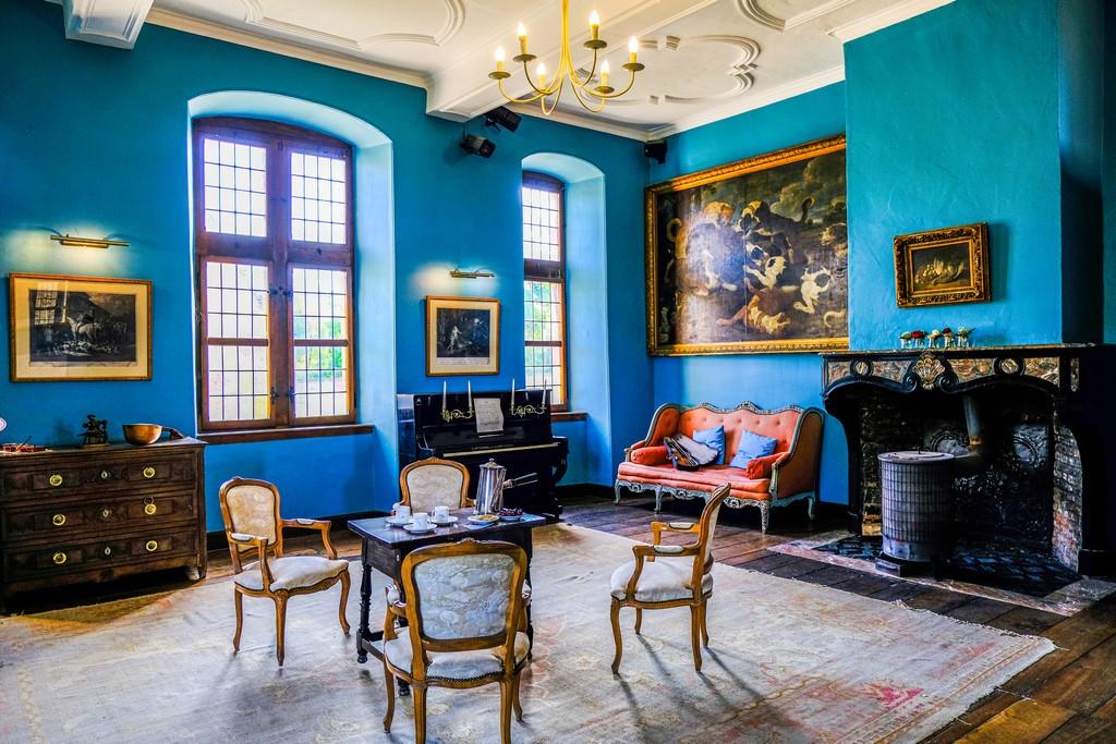 sala azzurra con tavolo sedie pianoforte camino violino