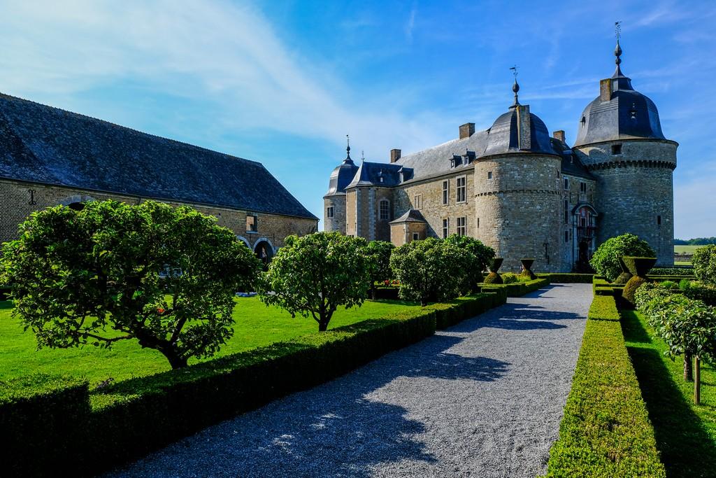 cortile esterno con alberi bassi e aiuole vista su castello in lontananza