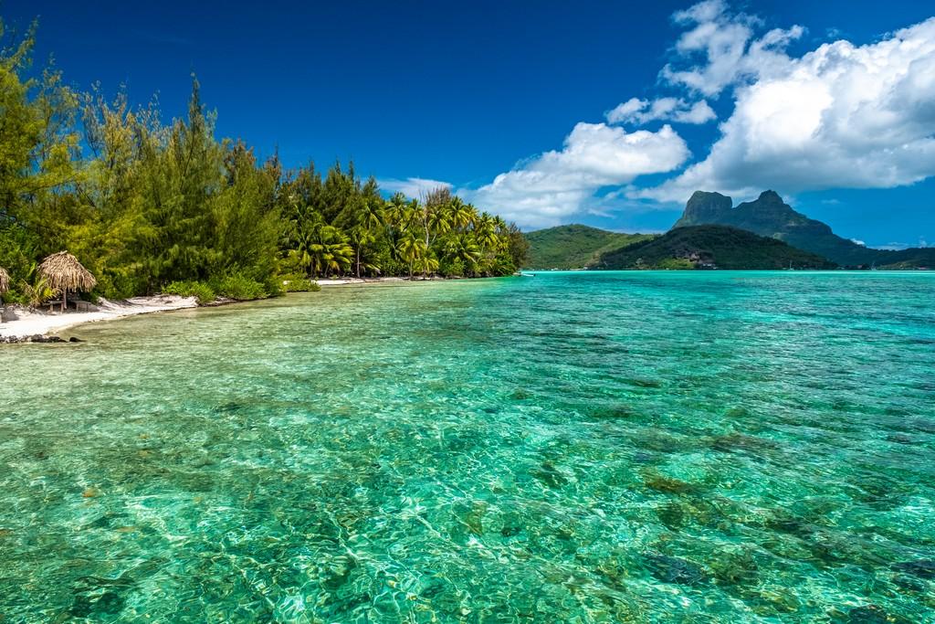Visitare la laguna di Bora Bora laguna verde con isole montuose sullo sfondo