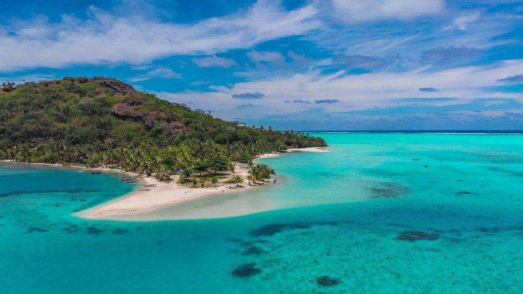 Maldive o Polinesia Francese vista aerea di una spiaggia con mare turchese e isola collinare