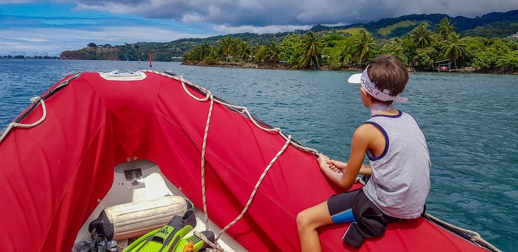 bambino cavalca un gommone rosso al largo della costa nord di Tahiti