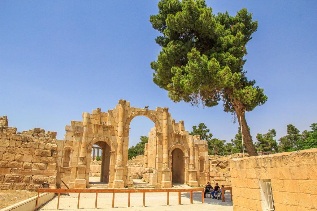 porta dell'antica città romana con albero e persone all'ombra