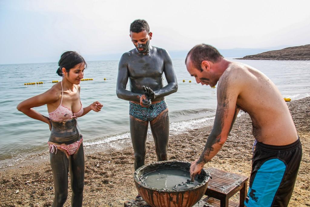 una donna e due uomini si spalmano di fango curativo