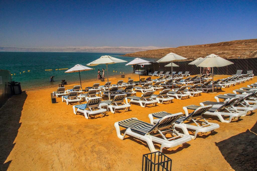spiaggia sulla costa mar morto con lettini e ombrelloni