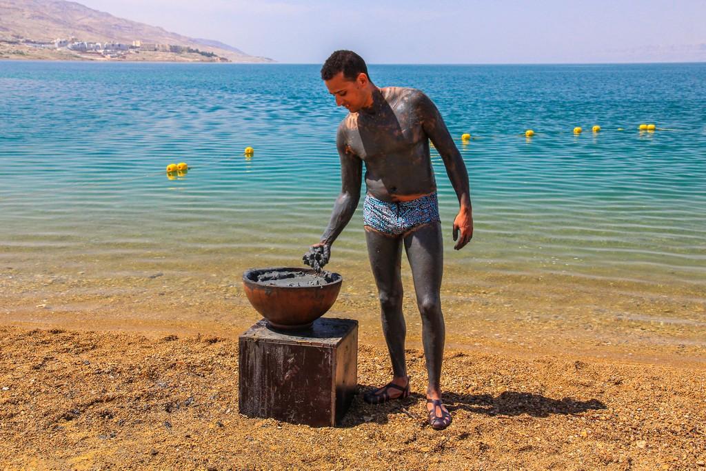 uomo si spalma di fanghi sulla costa del mar morto