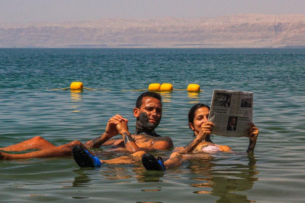 coppia legge il giornale galleggiando sull'acqua