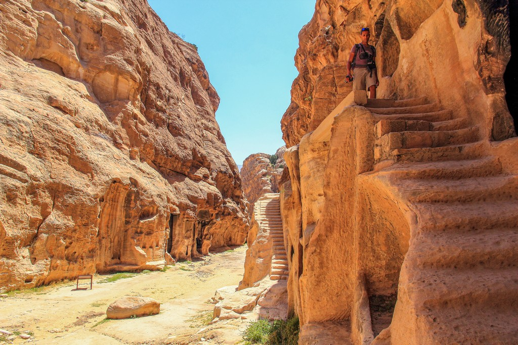 persona che scende dalla scalinata con altra scalinata in secondo piano dentro un canyon