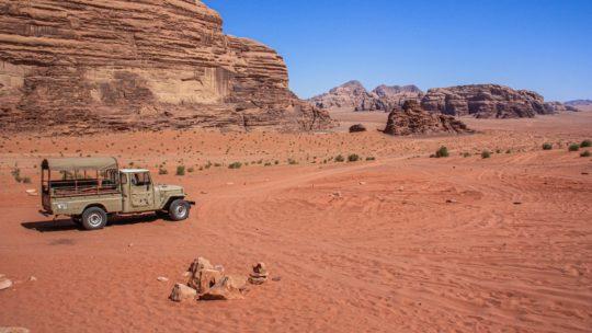 sabbia rossa e colline rocciose del deserto giordano con jeep