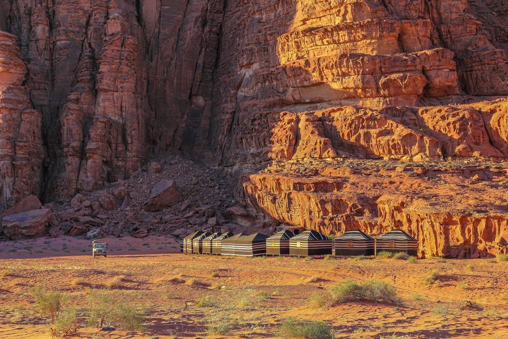 sabbia rossa e colline rocciose del deserto giordano con accampamento beduino