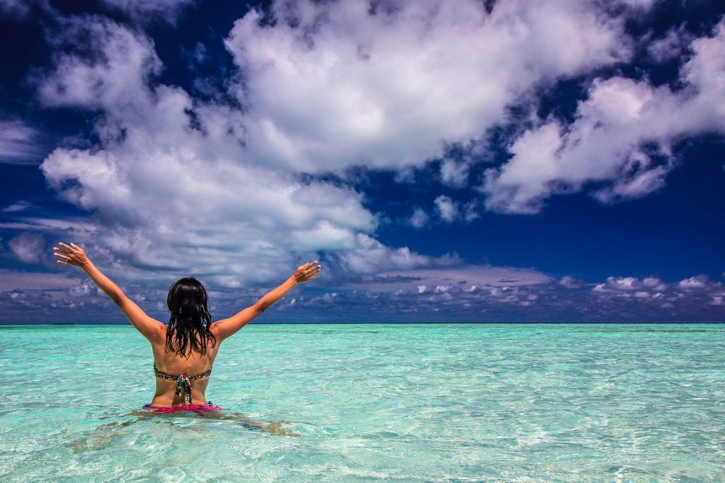 Maldive o Polinesia Francese donna in laguna azzurra