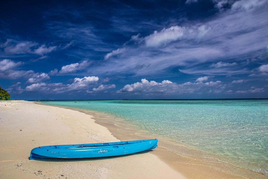 Maldive o Polinesia Francese spiaggia bianca e laguna azzurra con kayak blu