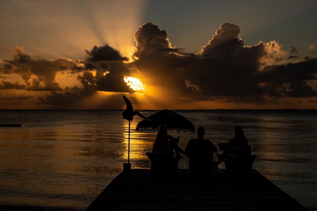 persone guardano il mare al tramonto