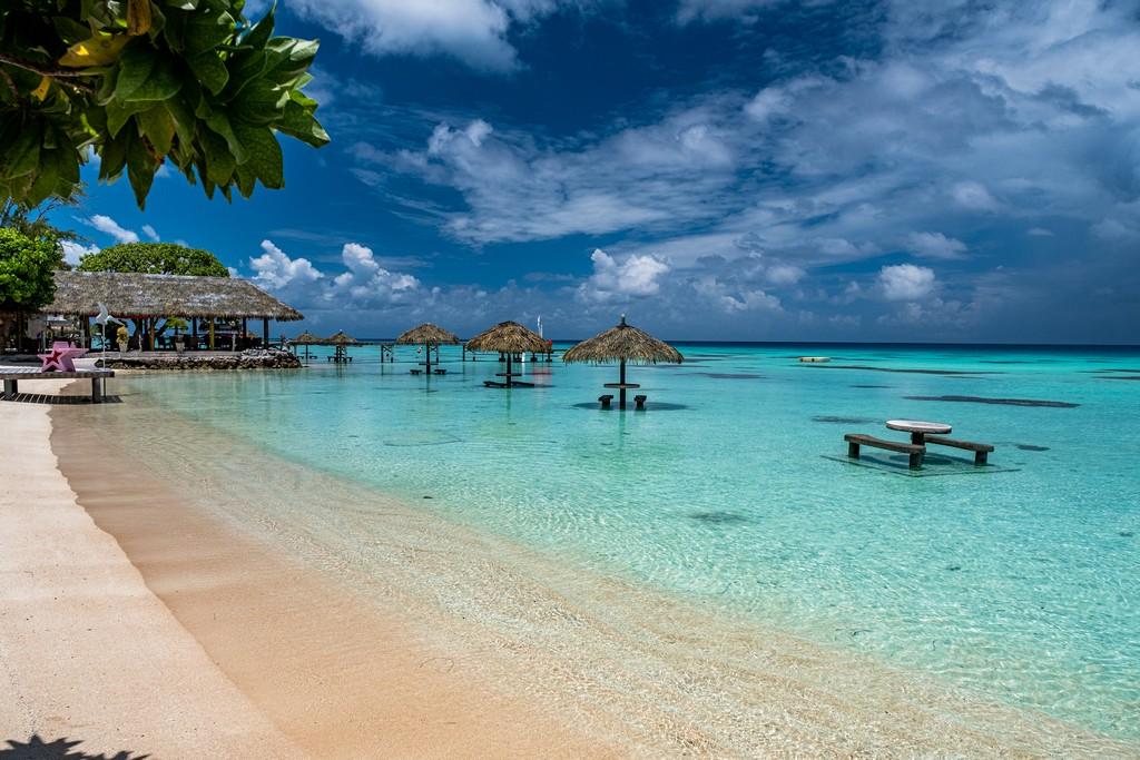 spiaggia con ombrelloni di pagglia nell'acqua