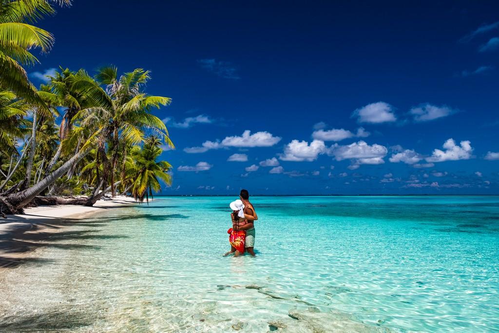 coppia in una spiaggia con palme guarda indietro