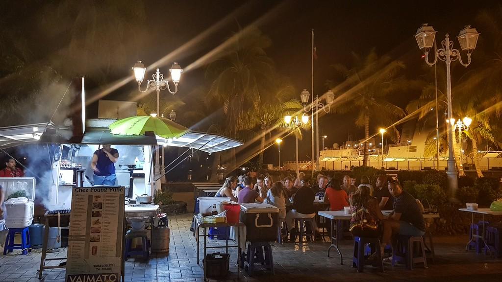 food truck all'aperto di sera con clienti seduti ai tavoli