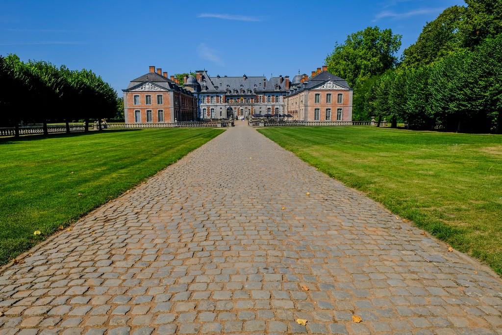 sentiero di accesso in pave verso il castello con alberi e prato ai lati