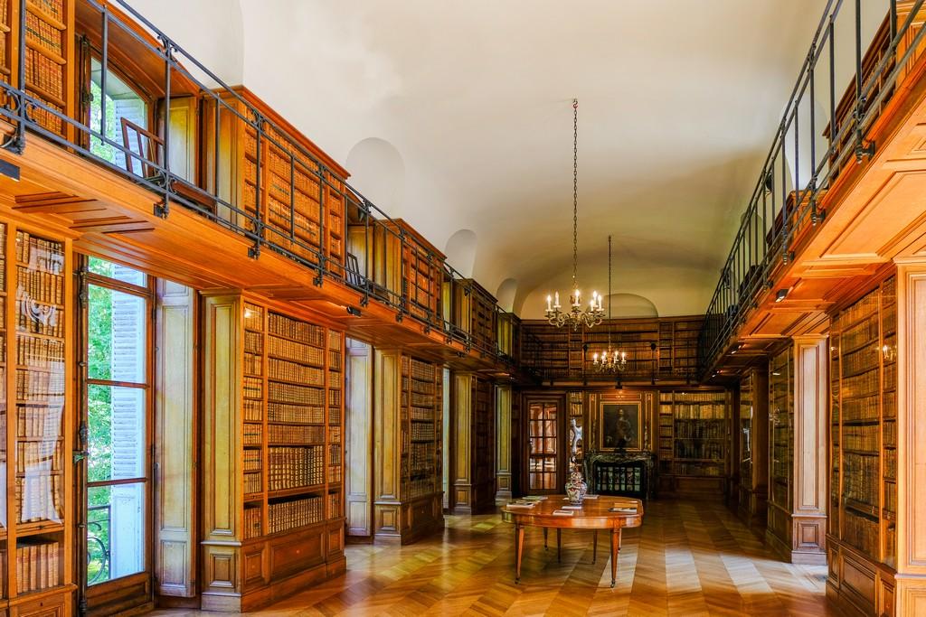 biblioteca con libri su tutti i lati soffitto crema e lampadari