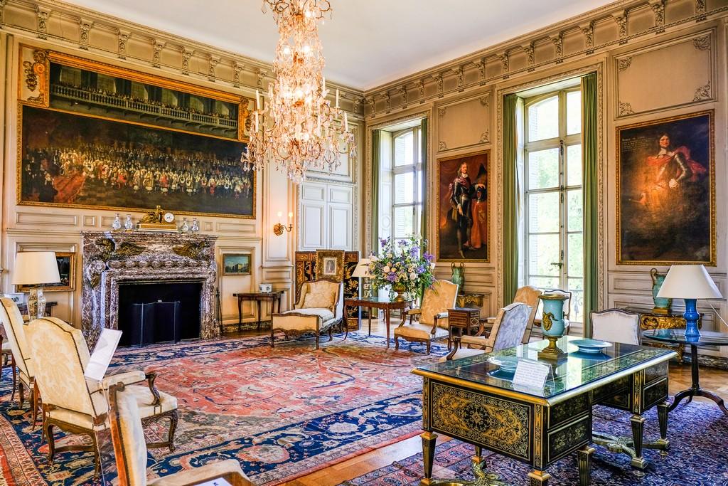 vista di una stanza interna con scrittoio laccato sedie imbottite lampadario tappeti quadri e finestre a tutta altezza