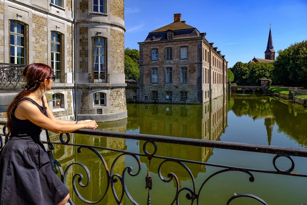 ragazza guarda il riflesso del castello nell'acqua con la chiesa in fondo