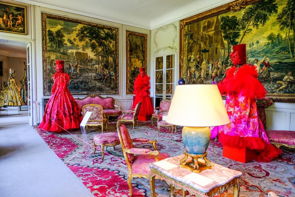 manichini vestiti di abiti rossi in una stanza con sedie e divani imbottiti di rosso e consolle con abatjour