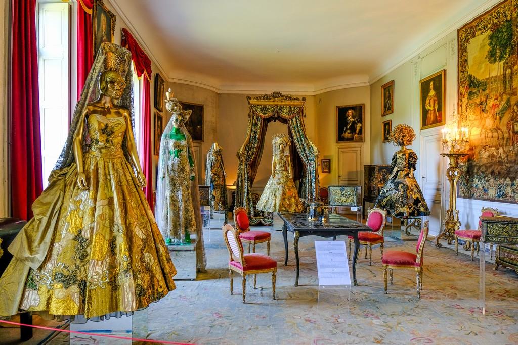 manichini in abiti dorati in sala con letto a badacchino, arazzi quadri tavolo e sedie imbottite