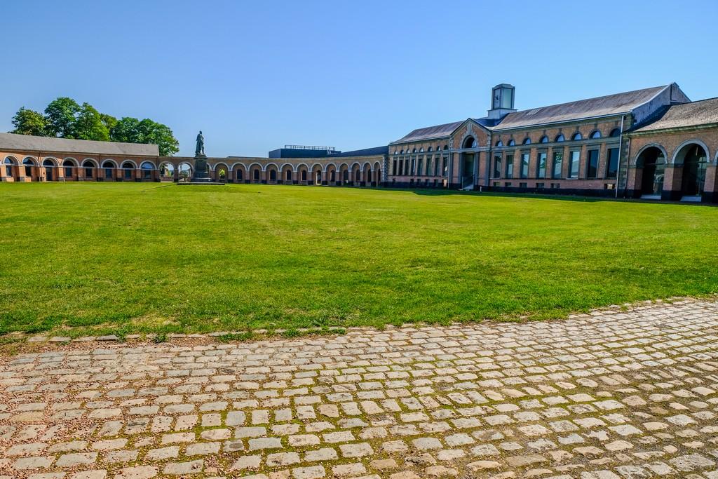 piazza ovale con prato statua al centro ed edifici sui lati con arcate