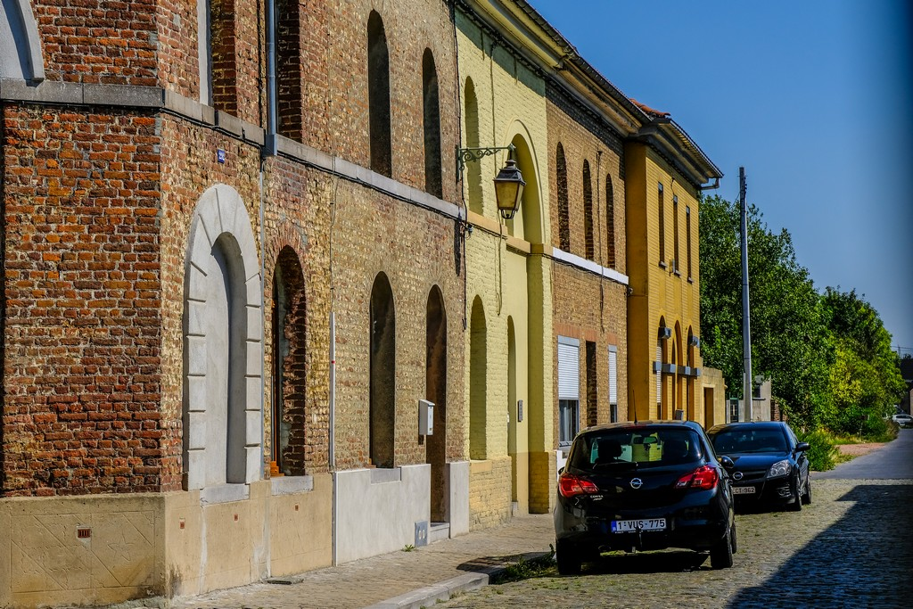 mura di mattoncini rossi e gialli con auto parcheggiate