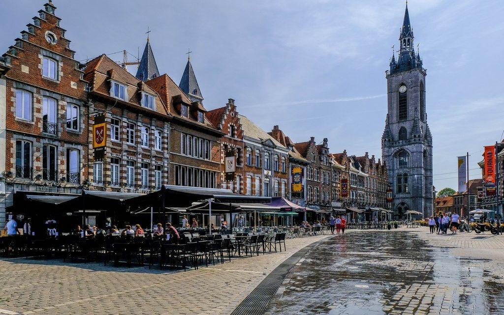 visita a tournai grand place con beffroi e case e sole vista frontale