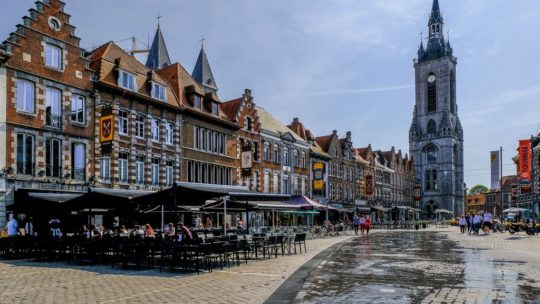 visita a tournai grand place con beffroi e case e sole vista frontale
