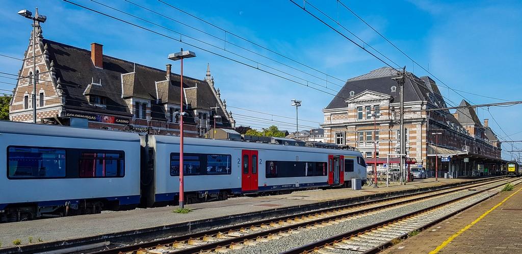 vista della stazione ferroviaria dall'interno con treno in attesa in banchina e binari
