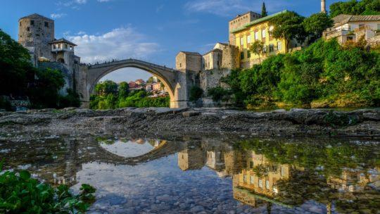 Cosa vedere a Mostar ponte vecchio di mostar riflesso in una pozza dacqua sulle rive