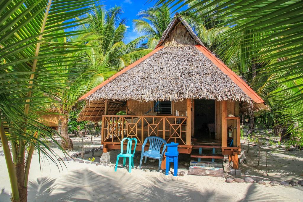 bungalow con sedie di plastica davanti sotto le palme