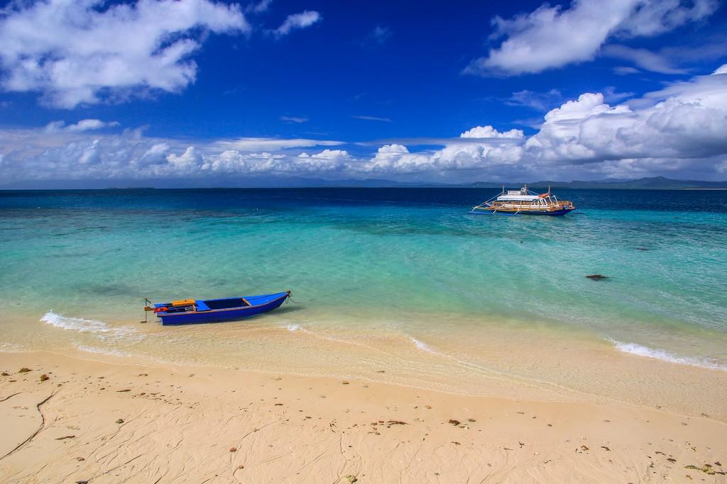 spiaggia con barche e nuvole bianche