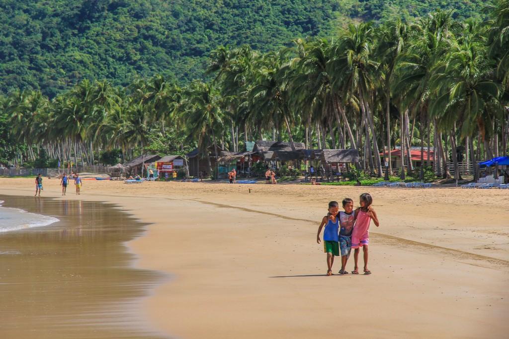 bambini in spiaggia con palme