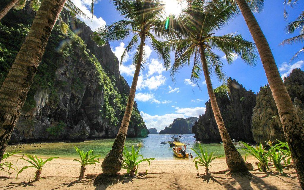 spiaggia con mare cristallino e montagne e palme
